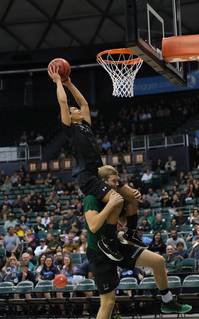 Hawaii volleyball player 'Eleu Choy attempts a dunk while riding on the shoulders of James Anastassiades during halftime of the Hawaii-Maine basketball game at the Stan Sheriff Center, Honolulu, Hawaii on December 29, 2019.