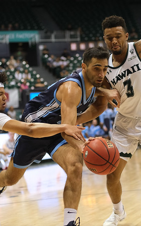 Maine's Sergio El Darwich drives between Hawaii's Drew Buggs and Eddie Stansberry (3) in the first half at the Stan Sheriff Center, Honolulu, Hawaii on December 29, 2019.