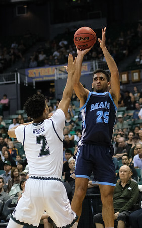 Maine's Sergio El Darwich shoots over Hawaii's Justin Webster at the Stan Sheriff Center, Honolulu, Hawaii on December 29, 2019.