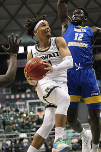 Drew Buggs of Hawaii hangs as Amadou Sow of UCSB tries to block his shot at the Stan Sheriff Center, Honolulu, Hawaii on January 18, 2020.