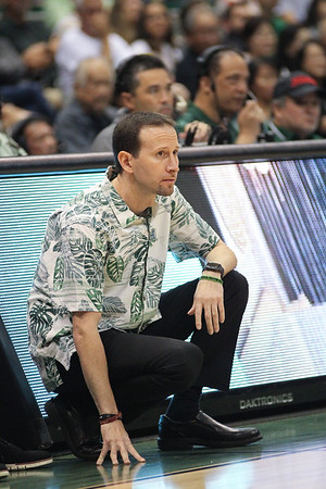 Hawaii coach Eran Ganot kneels before the scorer's table during a game against UCSB at the Stan Sheriff Center, Honolulu, Hawaii on January 18, 2020. Hawaii won, 70-63.
