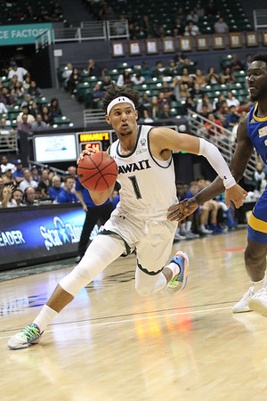 Drew Buggs drives past Amadou Sow at the Stan Sheriff Center, Honolulu, Hawaii on January 18, 2020.