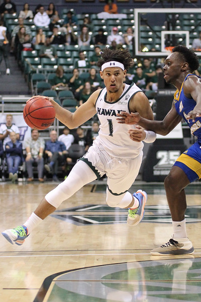 Drew Buggs (1) drives on Devearl Ramsey (4) at the Stan Sheriff Center, Honolulu, Hawaii on January 18, 2020.