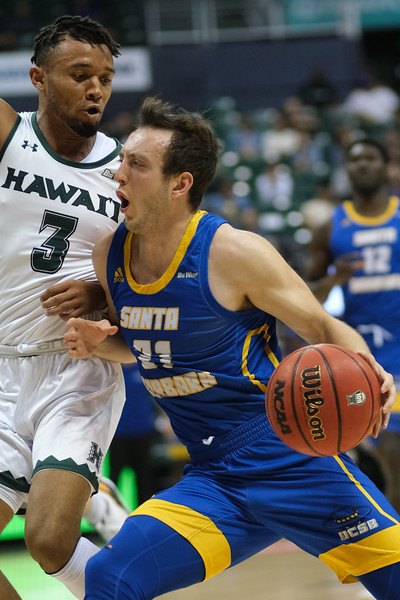 Max Heidegger (21) of UCSB drives on Eddie Stansberry (3) of Hawaii at the Stan Sheriff Center, Honolulu, Hawaii on January 18, 2020. Heidegger led the Gauchos with 21 points on 8-15 shooting.
