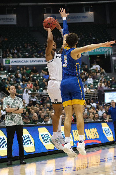 Eddie Stansberry shoots over Jaquori McLaughlin as both teams' head coaches look on at the Stan Sheriff Center, Honolulu, Hawaii on January 18, 2020.