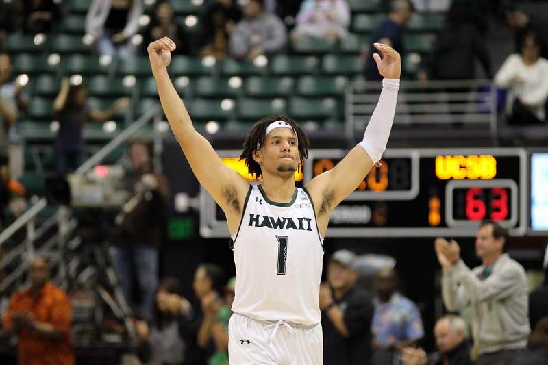 Drew Buggs raises his arms in the air as the final buzzer sounds at the Stan Sheriff Center, Honolulu, Hawaii on January 18, 2020. Hawaii beat UCSB, 70-63, and the fans received free tacos.
