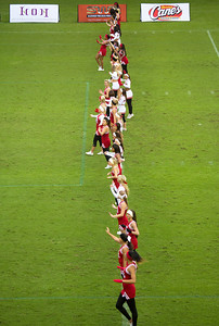 All the cheerleaders and dance line people form a chain across the field.