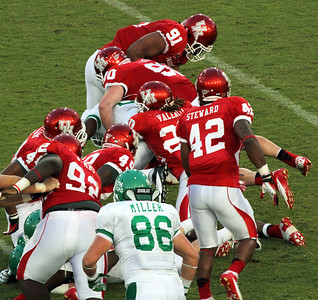 A UNT rusher is smothered by Cougar defense