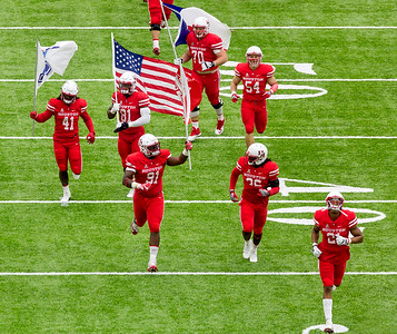 The UH  team runs their flags into the stadium.