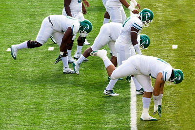 The Tulane players are doing their stretching exercises.