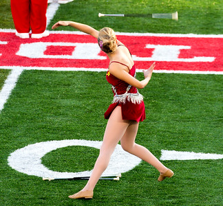 A cheerleader does a tricky behind-the-back baton catch.