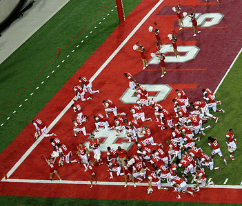 Odd juxtaposition: The Houston Cougars praying, surrounded by cheerleaders.