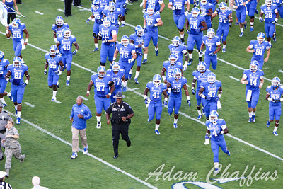 Coach Joker Phillips and the UK football team charge the field before the UK vs. Kent State football game at Commonwealth Stadium, Photo by Adam Chaffins