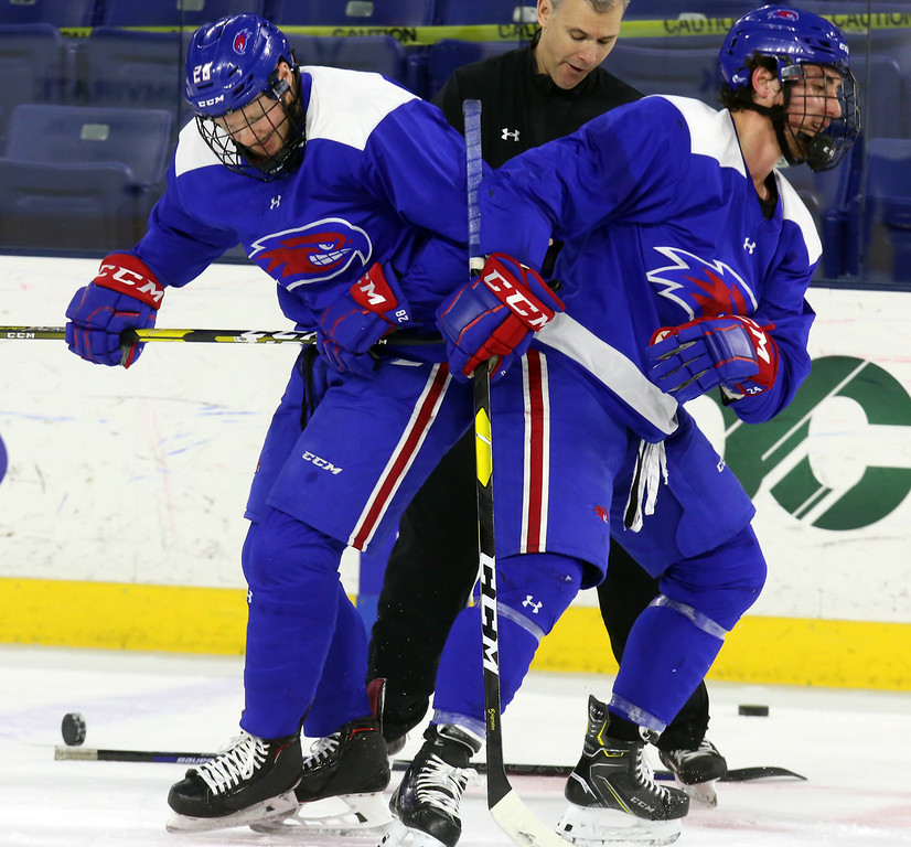 . UMass Lowell hockey practice. Coach Norm Bazin drops pucks for faceoff drills between Connor Sodergren (28), left, and Lucas Condotta (24), right. (SUN Julia Malakie)