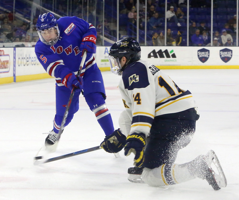 . UMass Lowell vs Merrimack College hockey. UML\'s Chase Blackmun (5) shoots past Merrimack\'s Patrick Kramer (14), setting up a goal by teammate Reid Stefanson in the second period which gave UML a 4-3 lead. (SUN Julia Malakie)