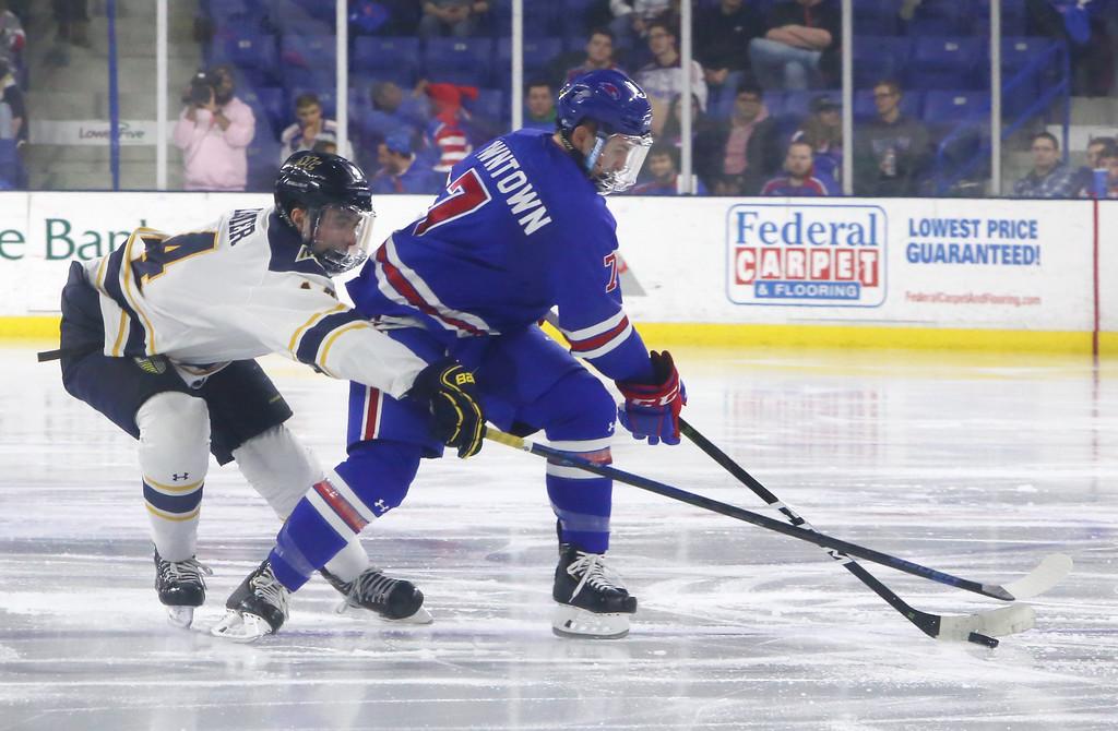 . UMass Lowell vs Merrimack College hockey. Merrimack\'s Patrick Kramer (14) and UML\'s Kenny Hausinger (7). (SUN Julia Malakie)