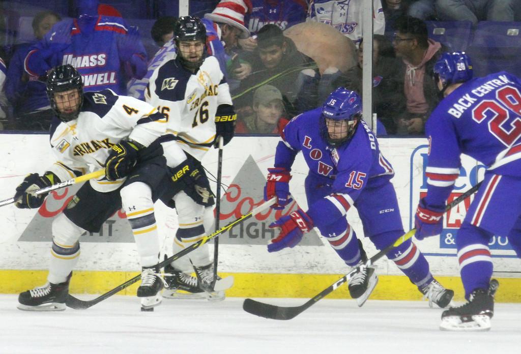 . UMass Lowell vs Merrimack College hockey. UML\'s Ryan Dmowski (15) and Connor Sodergren (28), and Merrimack\'s Tyler Drevitch (4) and Laine McKay (16). (SUN Julia Malakie)