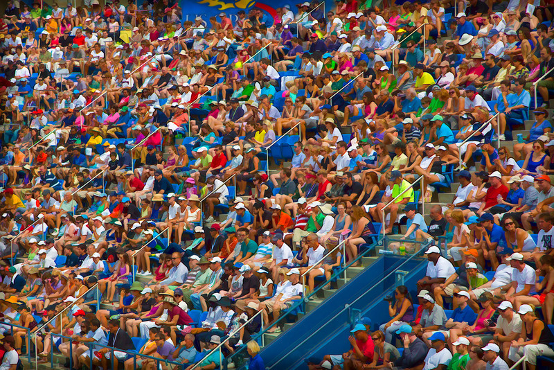 A crowd of fans in a full stadium watch a sporting event on a sunny summer day  in New York.  Middle Sunday at Louis Armstrong Stadium during the 2012 US Open tennis tournament.