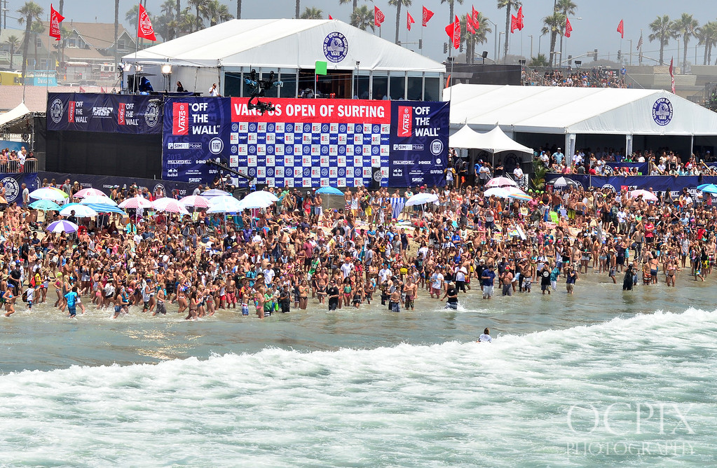 Crowds look on as pro surfers finish their heat