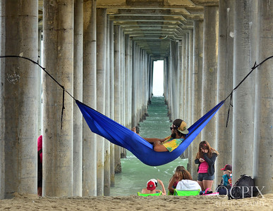 Man in hammock under the Huntington Beach Pier