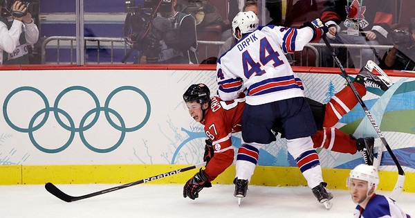 USA's Brooks Orpik (44) checks Canada's Sidney Crosby (87) into the boards in the third period of a preliminary round men's ice hockey game at the Vancouver 2010 Olympics in Vancouver, British Columbia, Sunday, Feb. 21, 2010. USA won 5-3. (AP Photo/Matt Slocum)