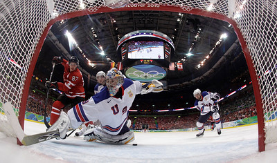 USA's goalie Ryan Miller (39) dives for a goal scored by Canada's Sidney Crosby,  left, in the third period of a preliminary round men's ice hockey game at the Vancouver 2010 Olympics in Vancouver, British Columbia, Sunday, Feb. 21, 2010. (AP Photo/Julie Jacobson)
