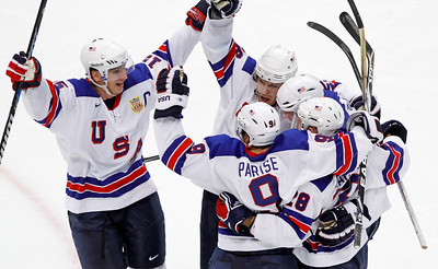 USA's Jamie Langenbrunner (15) is congratulated after scoring a goal during the third period of a preliminary round men's ice hockey game against Canada at the Vancouver 2010 Olympics in Vancouver, British Columbia, Sunday, Feb. 21, 2010. (AP Photo/Gene Puskar)