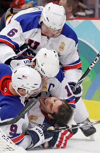 USA's Ryan Kesler (17) is congratulated by Erik Johnson (6), Zach Parise (9) and Jamie Langenbrunner (15) after Kesler scored an open net goal in the third period of a men's preliminary round ice hockey game against Canada at the Vancouver 2010 Olympics in Vancouver, British Columbia, Sunday, Feb. 21, 2010. (AP Photo/Chris O'Meara)