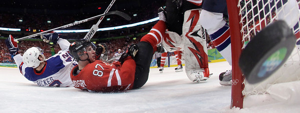 Canada's Sidney Crosby (87) sprawls on the ice as a shot by USA's Chris Drury scores in the second period of a preliminary round men's ice hockey game at the Vancouver 2010 Olympics in Vancouver, British Columbia, Sunday, Feb. 21, 2010. USA's David Backes (42) was also down. The USA won 5-3. (AP Photo/Julie Jacobson)