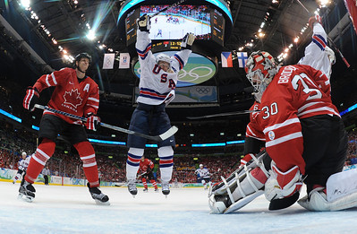 USA's Zach Parise, center, celebrates after USA's Jamie Langenbrunner, far right, scored past Canada's goalie Martin Brodeur in the third period in men's preliminary round hockey play at the Vancouver 2010 Olympics in Vancouver, British Columbia, Sunday, Feb. 21, 2010. Canada's Chris Pronger is at left. The USA won 5-3.  (AP Photo/Bruce Bennett, Pool)