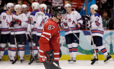 Canada's Sidney Crosby (87) passes the USA team after they beat Canada 5-3 in a men's preliminary round ice hockey game at the Vancouver 2010 Olympics in Vancouver, British Columbia, Sunday, Feb. 21, 2010. (AP Photo/Chris O'Meara)