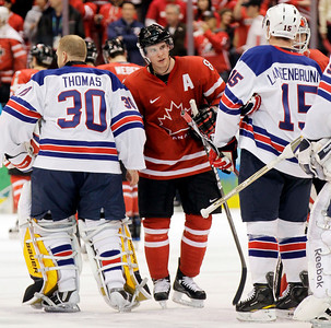 Canada's Sidney Crosby (87) shakes hands with USA goalie Tim Thomas (30) and Jamie Langenbrunner (15) after a preliminary round men's ice hockey game at the Vancouver 2010 Olympics in Vancouver, British Columbia, Sunday, Feb. 21, 2010. USA won 5-3. (AP Photo/Julie Jacobson)