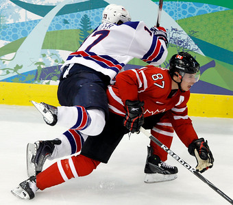 USA's Ryan Kesler (17) flips over Canada's Sidney Crosby (87)  during a preliminary round men's ice hockey game at the Vancouver 2010 Olympics in Vancouver, British Columbia, Sunday, Feb. 21, 2010. (AP Photo/Gene Puskar)