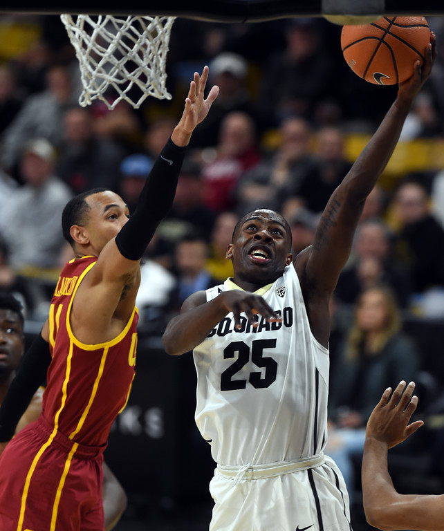 . McKinley Wright IV, of CU dives on Jordan McLaughlin, of USC, in the second half.  Cliff Grassmick / Staff Photographer/ February 21, 2018