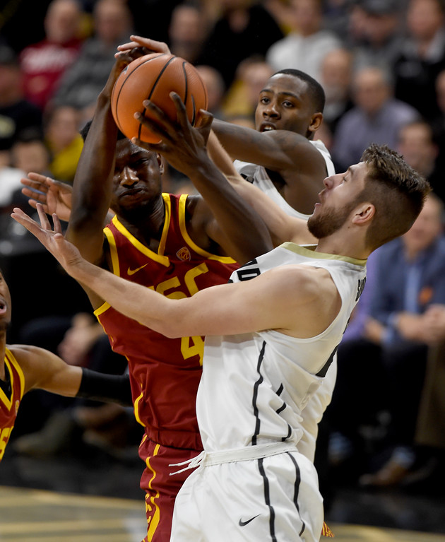 . Chimezie Metu, of USC, gets a rebound from Lucas Siewert, and McKinley Wright IV, of CU.   Cliff Grassmick / Staff Photographer/ February 21, 2018
