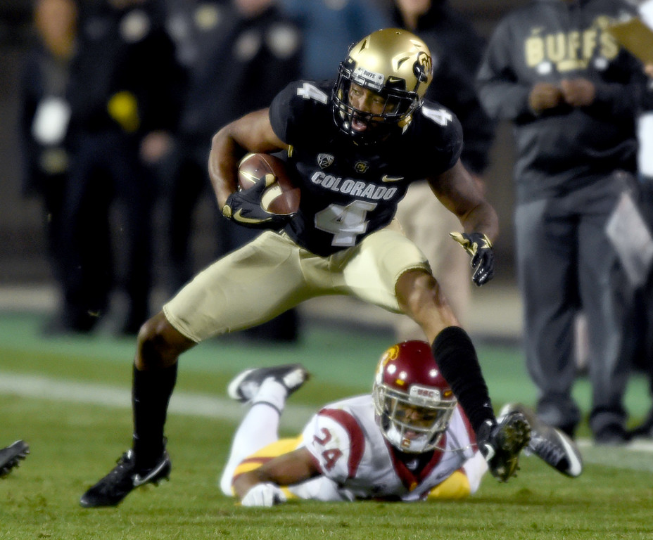 . Bryce Bobo, of CU, tries to spin away from USC defenders during the November 11th, 2017 game in Boulder.  Cliff Grassmick / Staff Photographer/ November 11, 2017, 2017