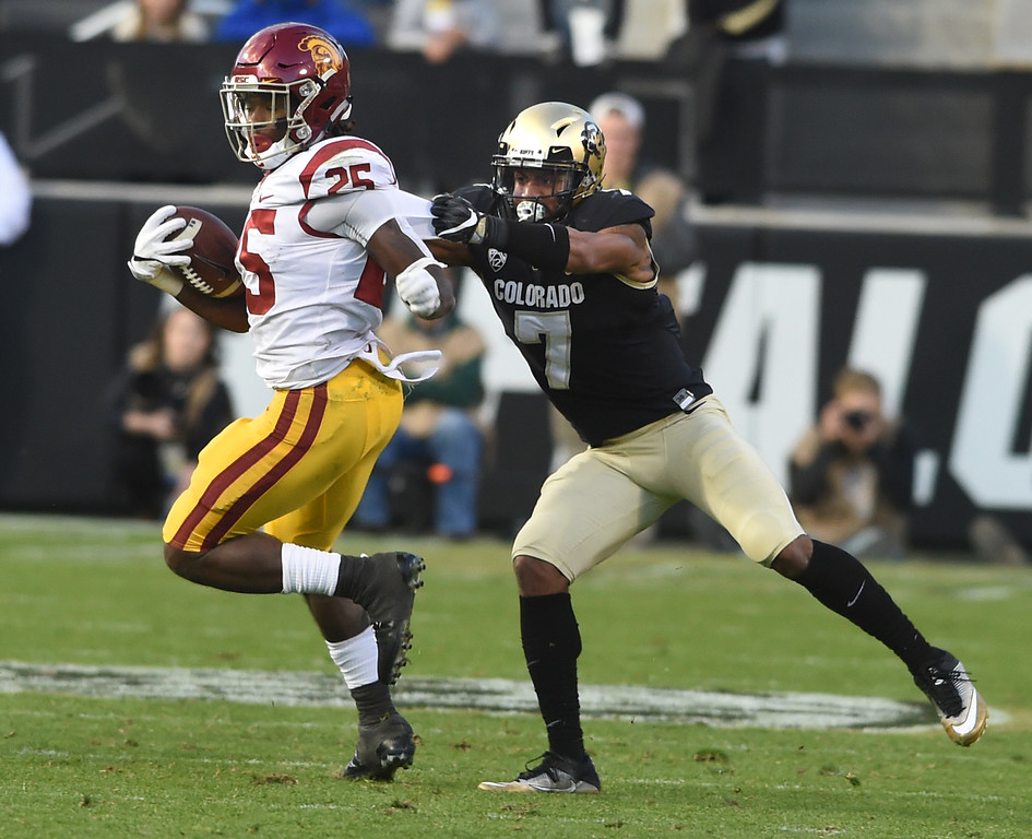 . Ronald Jones II, of USC, gets pulled down by Nick Fisher, of CU, during the November 11th, 2017 game in Boulder.  Cliff Grassmick / Staff Photographer/ November 11, 2017, 2017