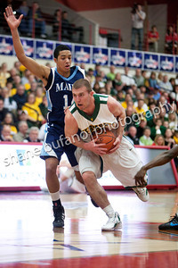 Brian Voelkel (23) of Vermont drives the lane as Justin Edwards of Maine defends him, during the Catamounts 50-40 win in an America East Conference Quarterfinal against Maine on March 3, 2012 at Chase Family Arena in Hartford, CT.