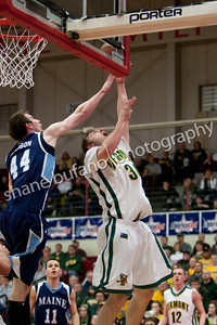 Matt Glass (right) attempts a lay up as he is defended by Mike Allison of Maine, during the Catamounts 50-40 win in an America East Conference Quarterfinal against Maine on March 3, 2012 at Chase Family Arena in Hartford, CT.