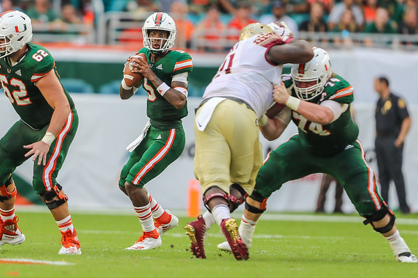 Miami Hurricanes quarterback N'Kosi Perry (5) drops for a pass as Miami Hurricanes offensive lineman Tyler Gauthier (74) and Miami Hurricanes offensive lineman Hayden Mahoney (62) hold the line.