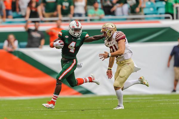 Miami Hurricanes wide receiver Jeff Thomas (4) shoves Florida State Seminoles punter Logan Tyler (21) during a regular season game at the Hard Rock Stadium.