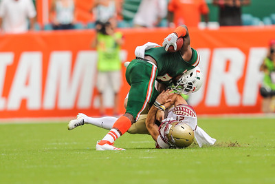 Miami Hurricanes wide receiver Jeff Thomas (4) battles for the ball against Florida State Seminoles punter Logan Tyler (21)