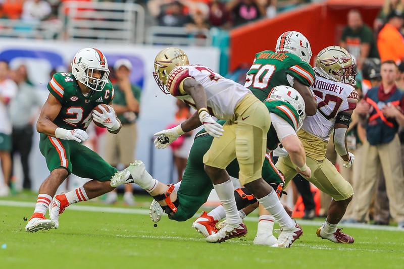 Miami Hurricanes running back Travis Homer (24) looks to run past a Florida State Seminoles defender.