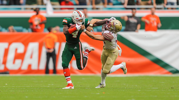 Miami Hurricanes wide receiver Jeff Thomas (4) battles for the ball against *Florida State Seminoles punter Logan Tyler (21)