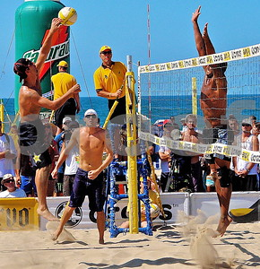 Ambidextrous Beach Star, USA Olympian Sean Rosenthal, spikes with his left hand past Fred Sousa as his Olympic teammate Jake Gibb looks on.  Beautiful Manhattan Beach Open where the surf meets the sand.