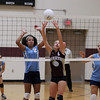 Record-Eagle/Keith King<br /> Traverse City Christian's Aubrey Heersema hits the ball as Grand Traverse Academy's Dakota Morgan, left, and Tiffany Wright, right, ready themselves Monday, September 10, 2012 at Traverse City Christian School.