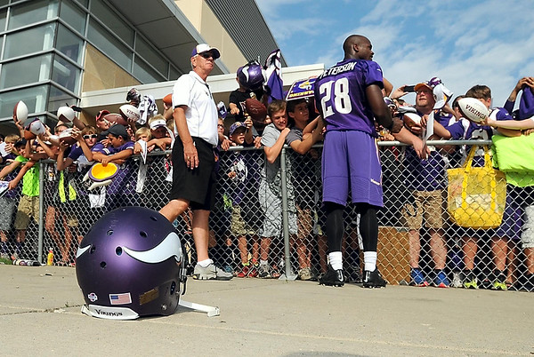 Minnesota Vikings running back Adrian Peterson set down his helmet to sign autographs after the team's last practice at Minnesota State University Thursday. Photo by Pat Christman