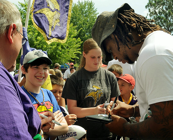 Viking defensive tackle Isame Faciane signs autographs for fans after arriving in Mankato on Thursday for the teams preseason training camp at Minnesota State University, Mankato. Photo by John Cross