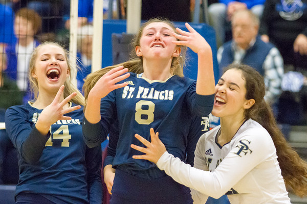 Record-Eagle/Brett A. Sommers Traverse City St. Francis' Maddie Connolly (8) reacts with teammates Kaylin Poole (14) and Ashlynn Coger (right) after a string of kills during Tuesday's Division 3 quarterfinal volleyball match against Beal City at Cadillac High School. St. Francis won 3-1.