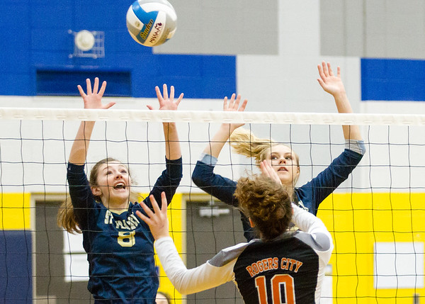 Record-Eagle/Brett A. Sommers Traverse City St. Francis' Maddie Connolly (8) and Brenna Poole (12) attempt to block the attack of Rogers City's Maddie Hincka during Tuesday's regional semifinal volleyball game in Gaylord. St. Francis won 3-1.